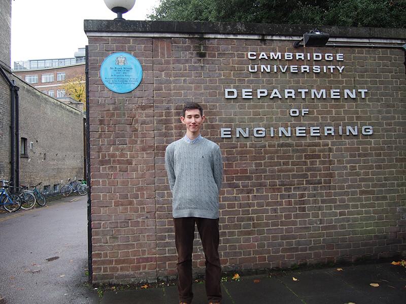 ケンブリッジ大学のカレッジ前に立つユング開さん